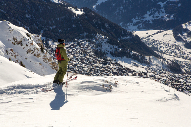 Skier standing above the town of Verbier.